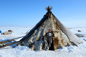 Carolina Serotetto, Nenet teenager standing at entrance of her reindeer fur covered tent, warmly dressed in traditional coat. Yar-Sale district. Yamal, Northwest Siberia, Russia. April 2016.  -  Eric Baccega