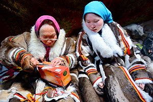 Two generations of Nenet women, an older woman and teenage girl, sewing and wearing traditional coats made of reindeer skin. Yar-Sale district, Yamal, Northwest Siberia, Russia. April 2016. - Eric Baccega