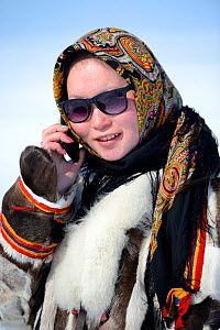 Carolina Serotetto, Nenet teenager wearing sunglasses and  traditional winter coat of reindeer fur holding smartphone. Yar-Sale district, Yamal, Northwest Siberia, Russia. April 2016.  -  Eric Baccega