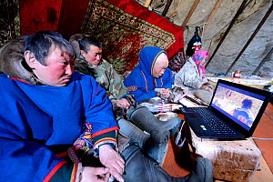 Nenet herders watching laptop inside tent. Yar-Sale district, Yamal, Northwest Siberia, Russia. April 2016.  -  Eric Baccega