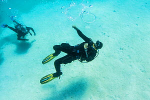 Dive instructor Ahmed Gomaa blows bubble rings whilst scuba diving at Dolphin House Reef, northern Red Sea, February 2016.  -  Bertie Gregory