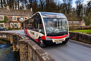 Rural public transport, a Cotswold Discoverer Bus on bridge in Northleach, Gloucestershire, UK. March 2014.  -  Nick Turner