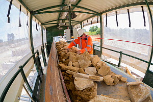 Hand selection of limestone for construction and dry stone walling, Huntsmans Quarry, Naunton, Gloucestershire, UK. July 2015. - Nick Turner
