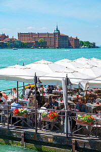 Diners on floating pontoon restaurant with Hilton Molino Stucky Venice on Giudecca Island in distance, Italy, April.  -  Gary  K. Smith