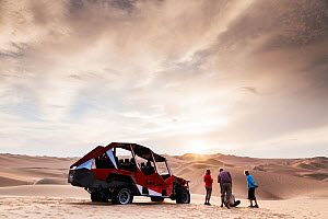 People stand with dune buggy in desert at Huacachina oasis, Ica region, Peru, December 2013. - Merryn  Thomas