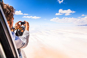 Man in vehicle, photographing Salar de Uyuni salt flats, Atacama Desert, Bolivia. February 2014.  -  Merryn  Thomas