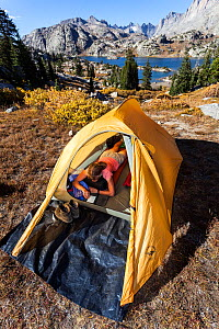 Camper reading inside tent above Island Lake, Wind River Range, Bridger Wilderness, Bridger National Forest, Wyoming, USA. September 2015. Model released.  -  Kirkendall-Spring