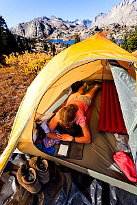 Woman Camper reading in tent above Island Lake, Wind River Range, Bridger Wilderness, Bridger National Forest, Wyoming, USA. September 2015. Model released.  -  Kirkendall-Spring