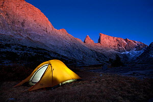 Tent lit up from inside, camping  in  Bridger Wilderness area of Wind River Range, Bridger National Forest, Wyoming, USA. September 2015. - Kirkendall-Spring