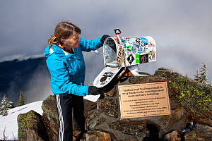 Woman looking inside the mailbox  on the summit of Mailbox Peak near North Bend, Washington, USA. March 2016. Model released.  -  Kirkendall-Spring