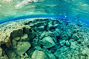 Scuba diver exploring Little Crack, almost like a miniature version of the main fissure, with both deep and shallow sections and many tunnels, Silfra Lagoon, Thingvellir National Park, Iceland.  -  Franco  Banfi