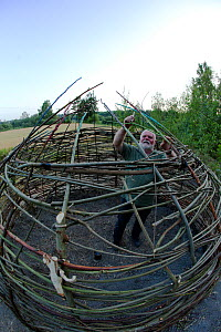 Artist Jan Erik Sorenstuen working on 'Syljusal', a framework of live willow which develops leaves and grows,  inspired by Bronze age housing. Valer. Ostfold County, Norway. July 2014. Model released. - Pal Hermansen
