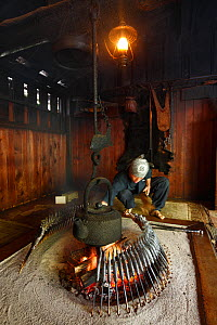 Man cooking in cabin which was used by Walter Weston who established alpinism mountaineering in Japan, Honshu, Japan. October 2008. - Cyril Ruoso