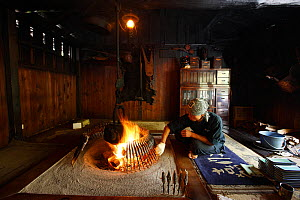 Man cooking trout in cabin which was used by Walter Weston who established alpinism mountaineering in Japan, Honshu, Japan. October 2008. - Cyril Ruoso