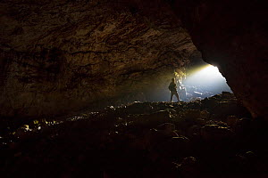 Caver at entrance to karstic cave in the Dinaric Alps, Slovenia. April 2016.  -  Alex  Hyde