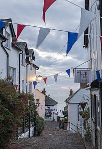 Bunting above cobbled streets in Clovelly at dawn, North Devon, England, UK. August 2012. - Adam Burton