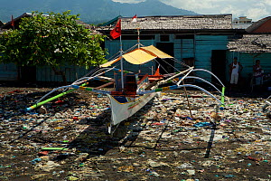 Trash covered beach with houses and boats at Tobelo Town, Halmahera, Indonesia. July 2008.  -  Tim  Laman