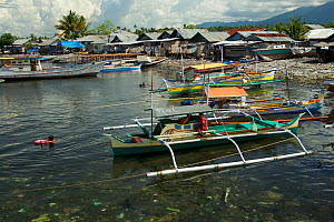 Litter strewn beach with houses and outrigger boats at Tobelo Town, Halmahera, Indonesia. July 2008.  -  Tim  Laman