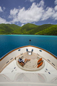 Woman relaxing in the stern of Watershed, 87-foot President Yacht with landscape of Saint John, U.S. Virgin Islands May 2012.  -  Billy  Black