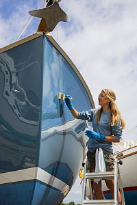 Woman painting her boat, USA, August 2013.  -  Billy  Black
