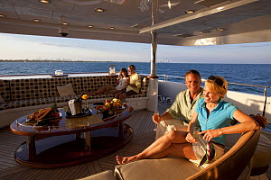 Couple relaxing on Glaze 161-foot Trinity Yacht, Miami, Florida, USA, March 2011. - Billy  Black