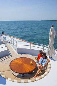 Couple relaxing aboard the yacht Glaze 161-foot Trinity in Miami, Florida, March 2011.  -  Billy  Black