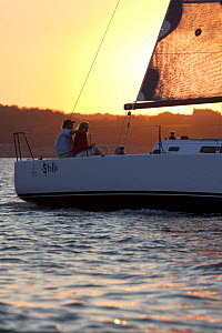 Couple on J/111 yacht sailing in Narragansett Bay at sunset. Rhode Island, USA, August 2010.  -  Billy  Black