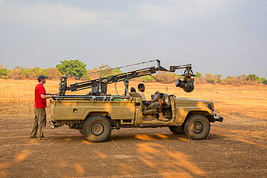 Wildlife cameraman Jamie McPherson, on filming vehicle - with 4K gyro stabilised cineflex suspended from a jib arm. On location to film BBC series 'The Hunt'. South Luangwa National Park, Zambia. Nove... - Huw Cordey