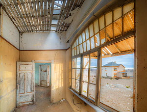 Abandoned homes in the diamond mining ghost town. Kolmanskop, near the Skeleton Coast, Namibia. June 2013. - Jack Dykinga