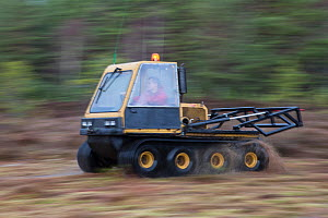 Person driving machine as part of peatland restoration project. Moss brash will be distributed on to bare peat, Inshriach, Glenfeshie, Cairngorms National Park, Scotland, UK, January 2015.  -  SCOTLAND: The Big Picture
