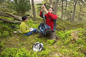 Field worker weighing Golden eagle (Aquila chrysaetos) chick with other field worker recording, Glen Tanar Estate, Aberdeenshire, Scotland, UK, June 2015. - SCOTLAND: The Big Picture