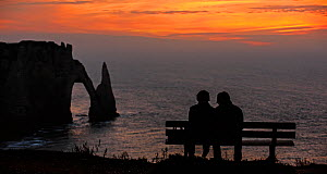 Elderly tourists sitting on bench looking at the Porte D'Aval, a natural arch in the chalk cliffs at Etretat at sunset, Cote d'Albatre, Upper Normandy, France, October 2015. - Philippe Clement