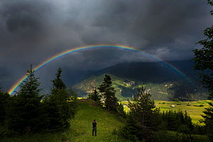 Photographer taking picture of rainbow and stormy sky over an Alpine meadow. Fiss Valley. Nordtirol, Tirol, Austrian Alps, Austria,  July 2015. - Nick Garbutt