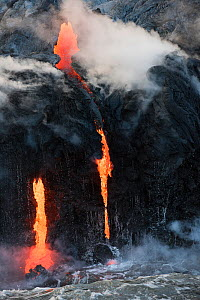 Hot lava from the 61G flow, emanating from Pu'u O'o on Kilauea Volcano, flows over sea cliffs and into the ocean through lava tubes at the Kamokuna ocean entry in Hawaii Volcanoes National Park, Kalap... - Doug Perrine