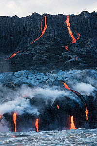 Hot lava from the 61G flow, emanating from Pu'uu O'o on Kilauea Volcano, flows over sea cliffs and into the ocean through lava tubes at the Kamokuna ocean entry in Hawaii Volcanoes National Park, Kala... - Doug Perrine