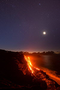 Hot  lava from the 61G flow, emanating from Pu'u O'o on Kilauea Volcano, flows over sea cliffs into the ocean under the stars and moon, Kamokuna, Kalapana, Hawaii Volcanoes National Park, Puna, Hawaii...  -  Doug Perrine