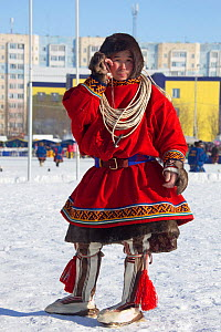 Young Nenets man on a mobile phone wearing traditional reindeer skin clothing during the reindeer herders' festival at Nadym. Yamal, Western Siberia, Russia - Bryan and Cherry Alexander