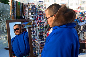 Nenets man trying on sunglasses at a stall at the reindeer herders' festival in Nadym. Yamal, Western Siberia, Russia - Bryan and Cherry Alexander
