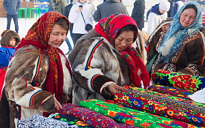 Nenets women shopping for material at a stall during the reindeer herders' festival in Nadym. Yamal, Western Siberia, Russia - Bryan and Cherry Alexander