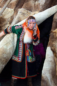 Young Nenets woman using a mobile phone emerging from  reindeer skin tent during the reindeer herders' festival in Nadym. Yamal, Western Siberia, Russia - Bryan and Cherry Alexander