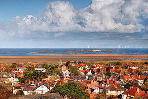 Hilbre Island and Little Hilbre in the Dee Ustuary viewed across the rooftops of West Kirby with wind turbines in the background Wirral, UK, April. - Alan  Williams