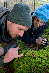 David Bavin and Josie Bridges inspecting scat of a Pine marten (Martes martes) reintroduced to Wales by the Vincent Wildlife Trust, Cambrian Mountains, Wales, UK, February 2016. Model released. - Nick Upton