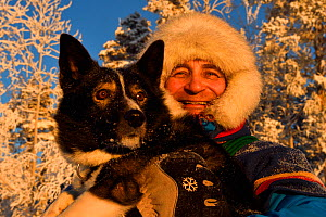 Nils-Torbjörn Nutti, owner and operator at Nutti Sami Siida, with domestic husky dog, during snowmobile trip into the wilderness, Jukkasjarvi, Lapland, Laponia, Norrbotten county, Sweden Model releas... - Staffan Widstrand