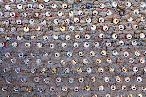 Hut wall built  with recycled  aluminium cans mixed with clay, making the walls very strong, Mababe village, Botswana - Christophe Courteau