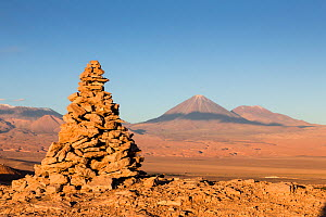 Apacheta / Apachita - a stone cairn in the Andes, a little pile of rocks built along the trail in the high mountains with Licancabur volcano (5916 m above sea level) and Juriques volcano to the far ri...  -  Christophe Courteau
