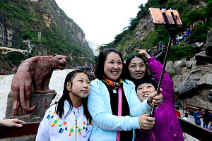 Chinese tourists taking  selfie photos in front of statue in Tiger Leaping Gorge, Haba Xue Shan Range. Yunnan, China, October 2016.. - Enrique Lopez-Tapia