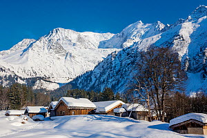 Winter in the French Alps with high altitude hamlet and Mont Blanc mountain range in background. Alpes, Haute-Savoie, France.  -  Klein & Hubert