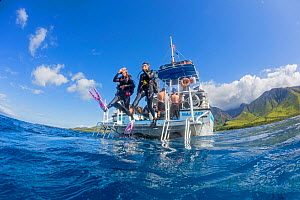 Divers step off a dive boat into the Pacific Ocean out from Ukumehame, Maui, Hawaii. March 2014.  Model released.  -  David  Fleetham