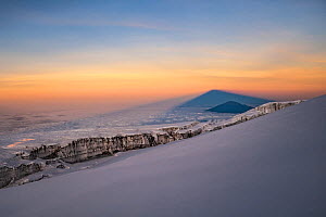 Mount Kilimanjaro casting shadow of Mount Meru at sunrise, Tanzania, May 2008 - Jen Guyton