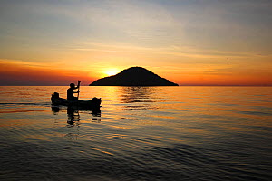 Fisherman rowing past the silhouette of Thumbe Island at sunset Lake Malawi, Cape Maclear, Malawi . June 2011  -  Jen Guyton